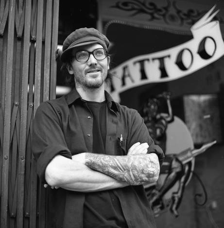 Man in front of Tattoo Shop