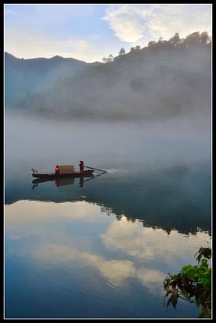 Fisherman in misty river