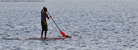 A YOLO board rider with a red paddle