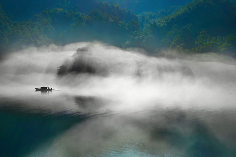 Fishing boat in misty river
